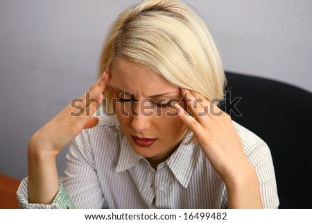 Woman with severe Headache (Migraine). holding hands to head