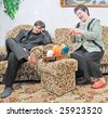 woman with sewing sit on sofa near man - stock photo
