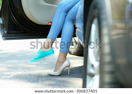 Woman with sexy legs in car, close-up - stock photo