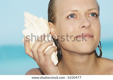 woman with shell to her ear - stock photo