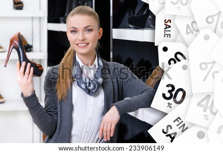 Woman with shoe in hand chooses stylish pumps looking at the shelves on Christmas sale - stock photo