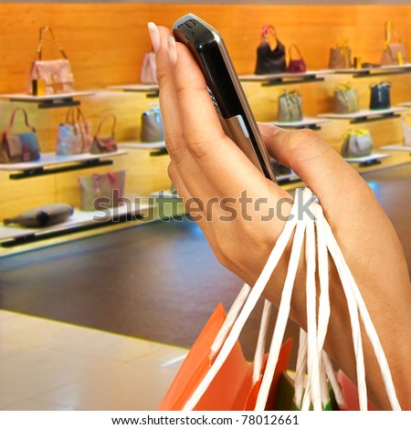 Woman With Shopping Bag And Holding Mobile Phone Shows Retail Purchasing In A Mall. A Store With Handbags To Buy Is In The Background.
