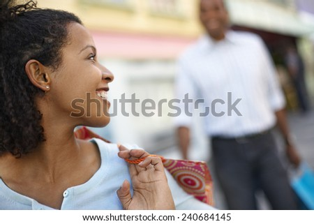 Woman with Shopping Bag Looking Back at Boyfriend - stock photo