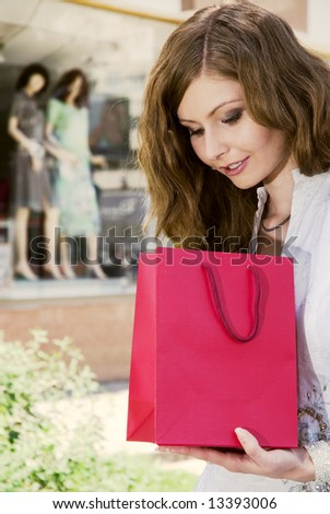 Woman with shopping bag looking what she had purchased