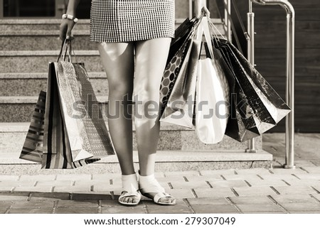 Woman with shopping bags against a mall steps - stock photo