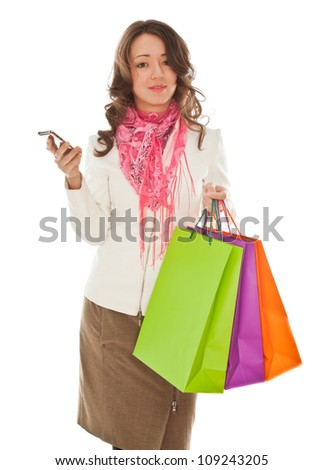 Woman with shopping bags calling by phone isolated on white - stock photo