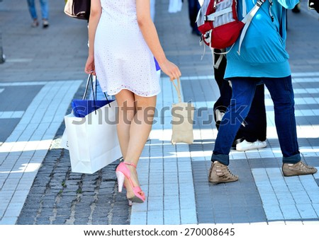 Woman with shopping bags in crowd - stock photo
