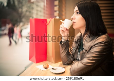 Woman with shopping bags in mall cafe drinking coffee.Shopaholic woman.Woman sitting alone in cafe.Businesswoman relaxing and enjoying after work,having a beverage.Image toned, noise added - stock photo