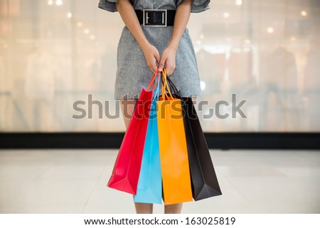 woman with shopping bags in mall, wearing a shirt
