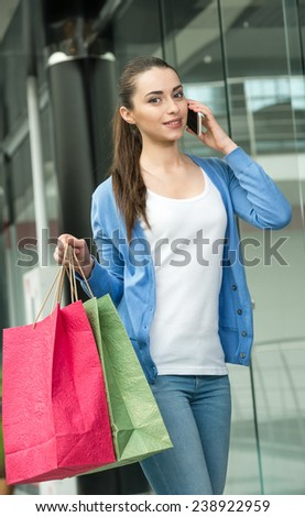 Woman with shopping bags is speaking by phone. - stock photo