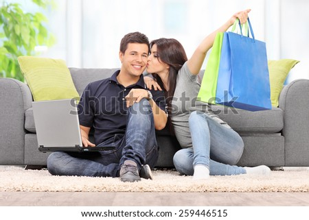 Woman with shopping bags kissing her boyfriend seated by a sofa at home - stock photo