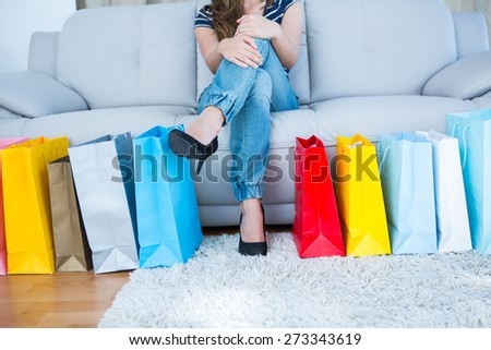 Woman with shopping bags on couch in the living room - stock photo
