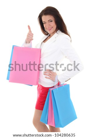 Woman with shopping bags showing thumbs up over white - stock photo