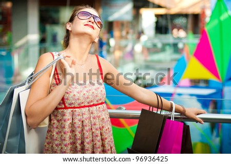 woman with shopping bags, smiling and walking
