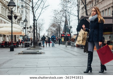 Woman with shopping bags walking on the street after buying - stock photo