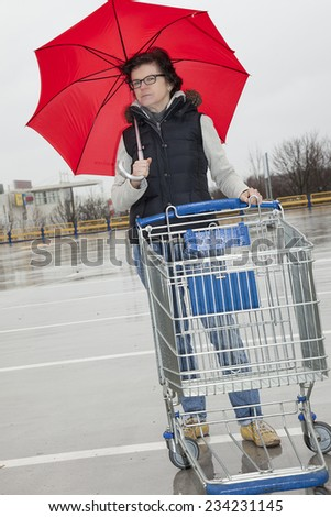 Woman with shopping cart and umbrella - stock photo