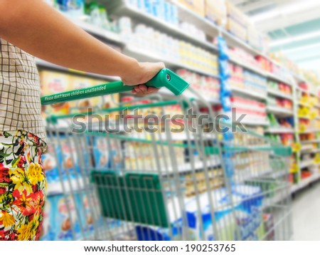 Woman with shopping cart in supermarket - stock photo