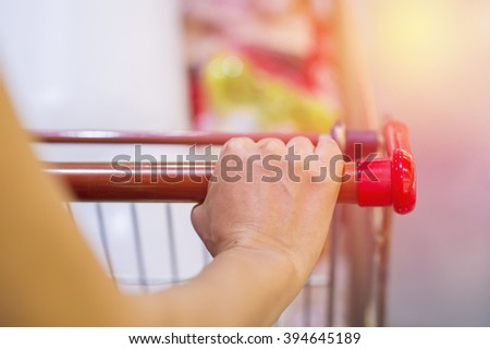 Woman with shopping cart. Vintage filter. - stock photo