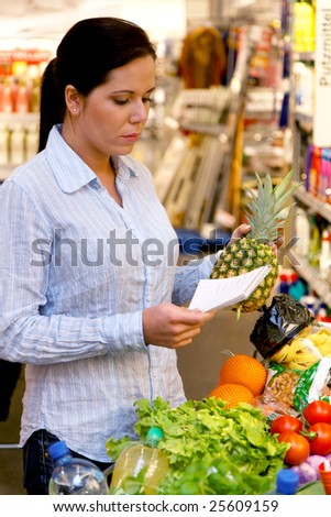 Woman with shopping list in a supermarket and shopping trolleys - stock photo