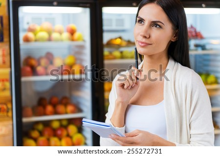 Woman with shopping list. Thoughtful young woman holding shopping list and looking away while standing in front of refrigerators in grocery store  - stock photo