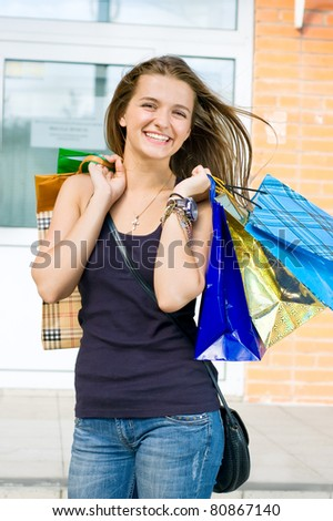 Woman with shopping out of the store - stock photo