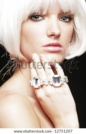 Woman with short cropped white hair and jewelry - stock photo