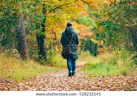 Woman with shoulder bag walking on path in autumn forest.
