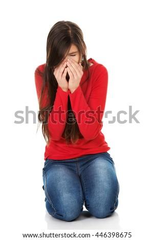 Woman with sinus pain sitting on the floor. - stock photo