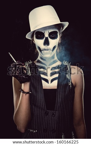 Woman with skeleton face art smoking over black background, conceptual photo - stock photo