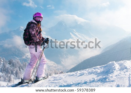 Woman with skis on the top of the mountain. Skiing in The Alps - stock photo