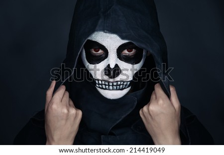 Woman with skull makeup in hood looks at camera, Halloween face art - stock photo