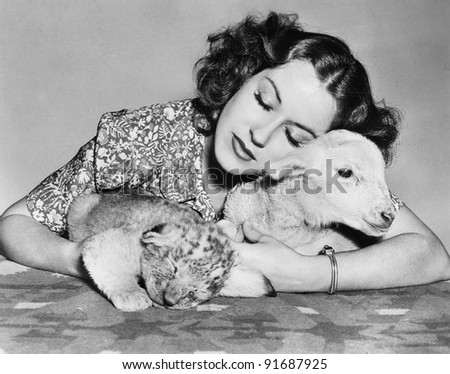 Woman with sleeping lamb and lion cub - stock photo