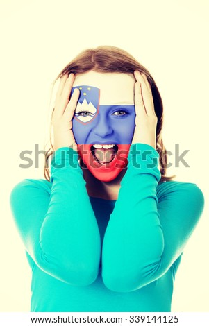 Woman with Slovenia flag painted on face. - stock photo