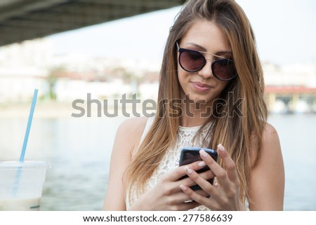 woman with smart phone on the river - stock photo
