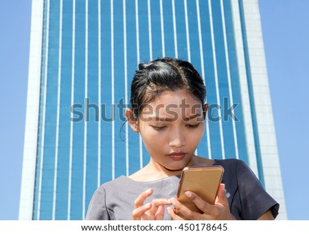woman with smart phone under skyscraper