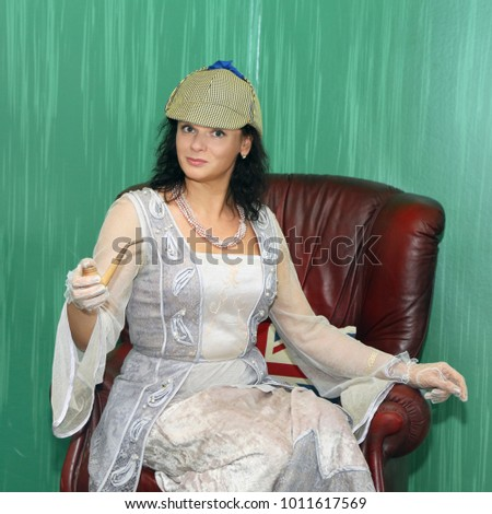 Woman with smoking pipe in hand sits in leather armchair imagining herself as Sherlock Holmes