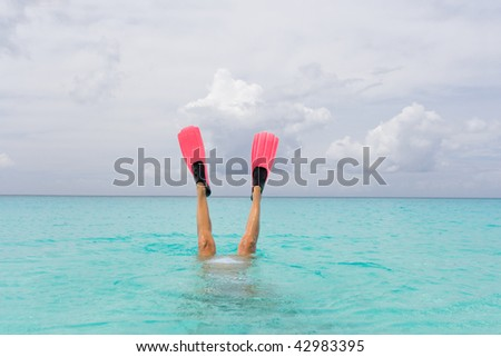 woman with snorkel fins diving in turquoise island water