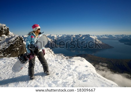 Woman with snowboard standing on top of snowy mountain - stock photo