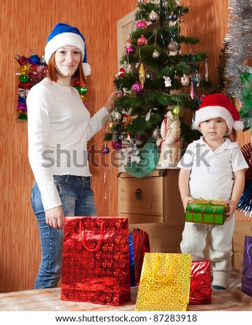 Woman with son in christmas hat near decoration spruce at home - stock photo