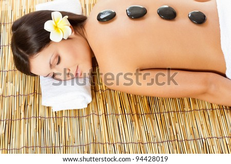 woman with spa stones on her back - stock photo