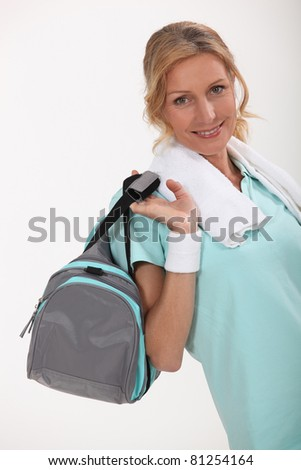 Woman with sports bag over shoulder - stock photo