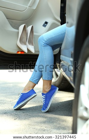 Woman with sporty legs in car, close-up - stock photo