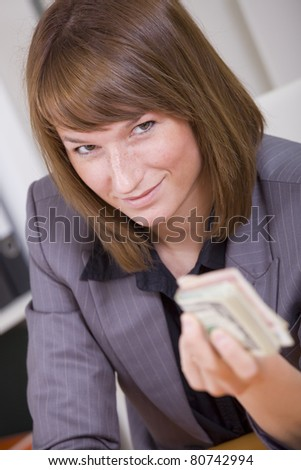 woman with stack of money - giving bribe or success business - stock photo