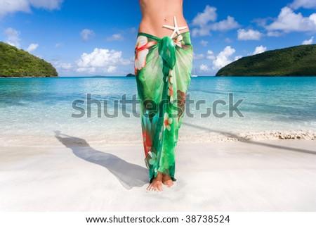 woman with starfish and green sarong on tropical beach - stock photo