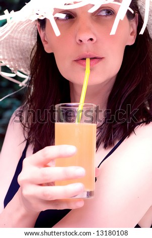 woman with straw hat drinking juice, close up, outside - stock photo
