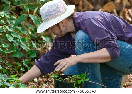 Woman with straw hat gardening - stock photo