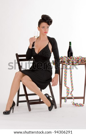 Woman with streamers and champagne sitting at the table when celebrating /Fashion trend - stock photo