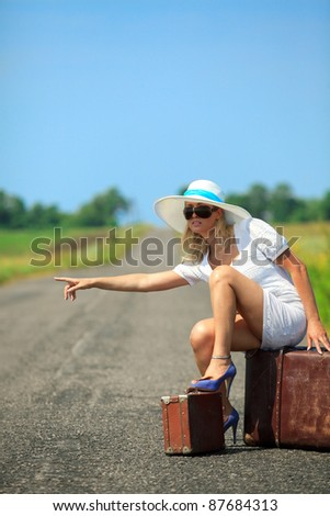 Woman  with suitcase with suitcase stops the car on countryside road - stock photo