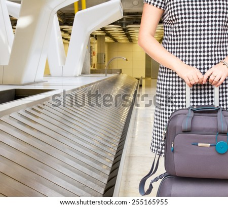 woman with suitcases close up close to airport luggage belt  - stock photo