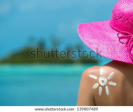 Woman with sun-shaped sun cream - stock photo